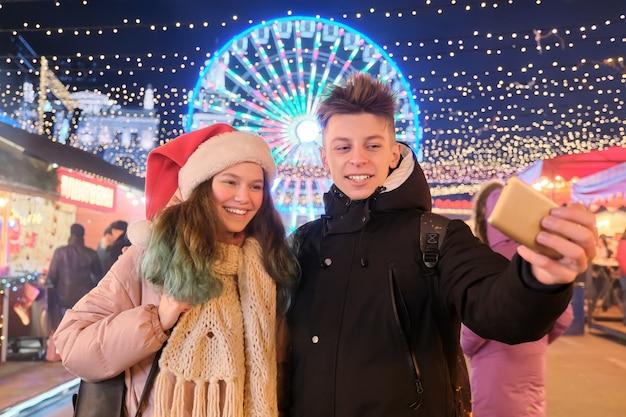 Weihnachtszeit, neujahrsfeiertage. junge leute, ein paar teenager, die spaß am weihnachtsmarkt haben