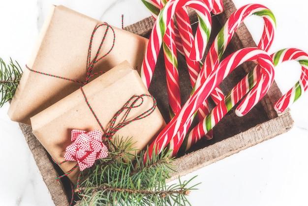 Weihnachtszeitkonzept, weihnachtsgeschenke und traditionelle süßigkeitenzuckerstange des neuen jahres in der alten holzkiste, auf einer weißen marmortabelle. draufsicht copyspace