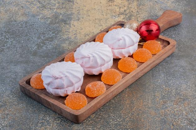 Weihnachtszephyr mit geleesüßigkeiten auf einem holzbrett. hochwertiges foto