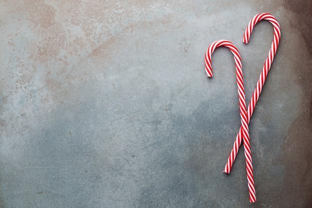 Weihnachtszuckerrohr lag auf blauem hintergrund. flache lage und draufsicht.