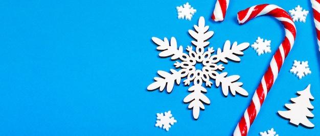 Weihnachtszuckerstange lag gleichmäßig in der reihe auf blau mit dekorativer schneeflocke und stern, ebenenlage und draufsicht