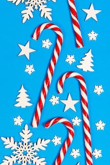 Weihnachtszuckerstange lag gleichmäßig in der reihe auf blau mit dekorativer schneeflocke und stern. flachlage und draufsicht