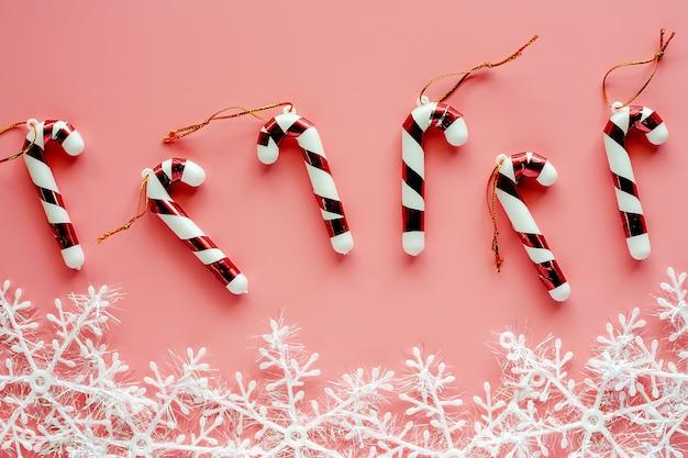 Weihnachtszuckerstange mit schneeflockenverzierungen auf rosa hintergrund für weihnachtstag und feiertage