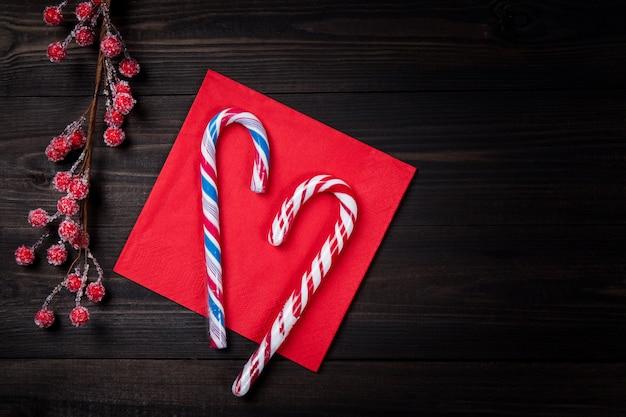 Weihnachtszuckerstangen auf roter serviette mit gefrorenen roten beeren auf dunklem holztisch.