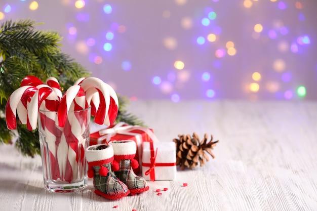 Weihnachtszuckerstangen im glas auf dem tisch auf hellem hintergrund