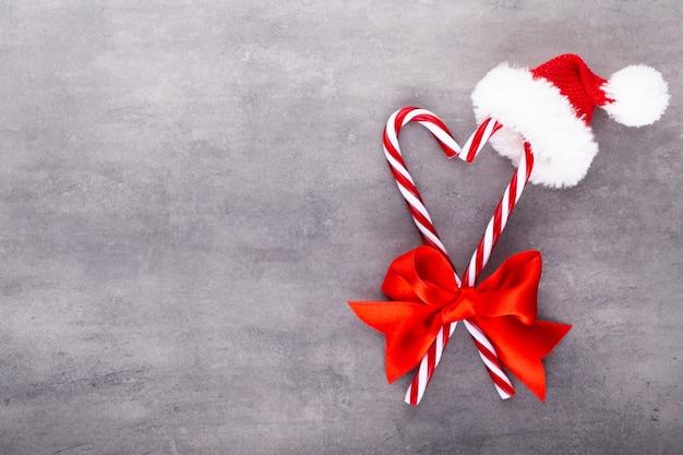 Weihnachtszuckerstangen, kleben und dekor auf farbigem hintergrund. süße weihnachtskarte - zuckerstangen mit band - bild.
