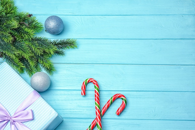 Weihnachtszuckerstangen und -dekor auf farbigem hölzernem hintergrund