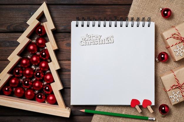 Weihnachtszusammensetzung aus offenem leerem notizblock und hölzernem weihnachtsbaum mit weihnachtskugeln im inneren