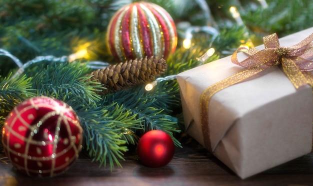 Weihnachtszusammensetzung aus roten und goldenen weihnachtskugeln, die fichtenzweige auf einer holzoberfläche verschenken