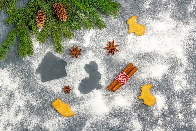 Weihnachtszusammensetzung. bemehlen sie schattenbild von plätzchen auf dunklem hintergrund unter weihnachtsbaumasten, kegeln, sternanis und zimt.