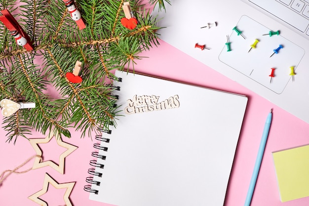 Weihnachtszusammensetzung des offenen leeren notizblocks, der tannenzweige und des laptops auf rosa papierhintergrund