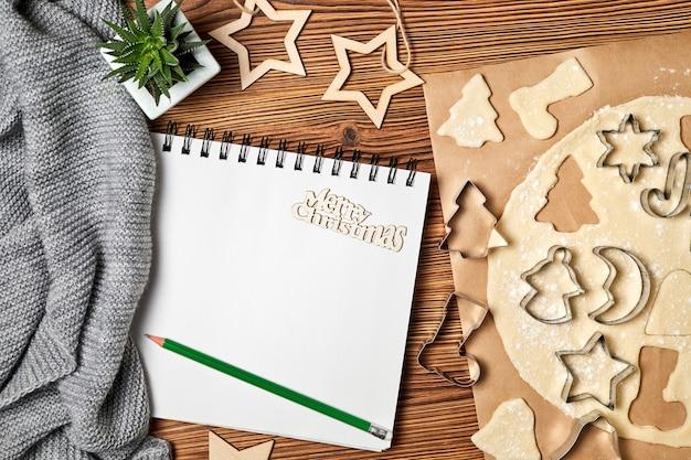 Weihnachtszusammensetzung des offenen leeren notizblocks roher lebkuchen-weihnachtsplätzchenschal und des kaktus