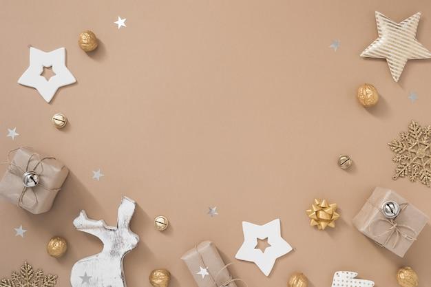 Weihnachtszusammensetzung. feld mit geschenken, handwerk und goldenen dekorationen auf beige pastellhintergrund.