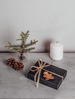 Weihnachtszusammensetzung geschenk schwarze und goldene dekorationen auf grauem steinhintergrund