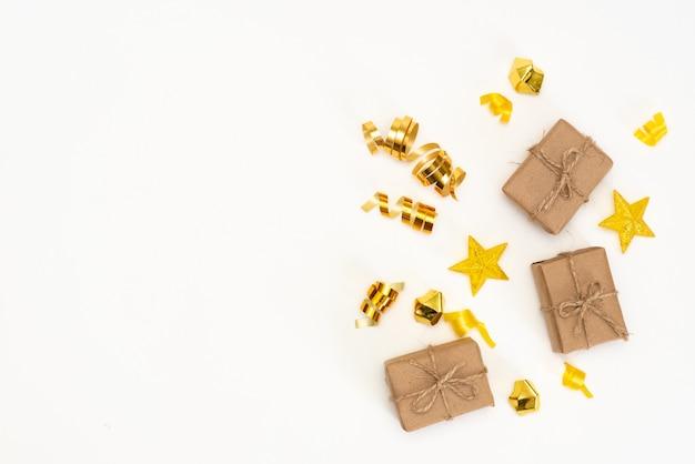 Weihnachtszusammensetzung. geschenk, weihnachtsgoldene dekorationen, zypressenniederlassungen, kiefernkegel auf weißem hintergrund. flachgelegt, draufsicht