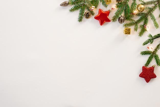 Weihnachtszusammensetzung, grenze, rahmen. weihnachtsdekorationen, tannenzweige und kegel, sterne und schneeflocken auf einem weißen hintergrund, draufsicht. flache position, kopie, raum. grußkarte