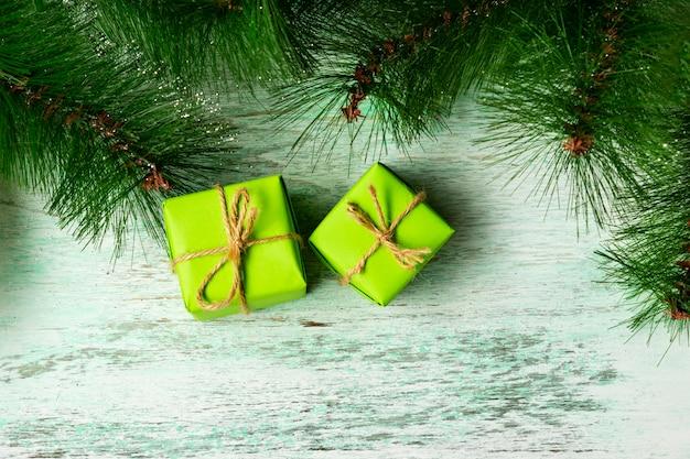 Weihnachtszusammensetzung. grüne geschenkboxen unter dem weihnachtsbaum onwooden boden nahe tannenzweigen. ansicht von oben. weihnachtsgeschenk