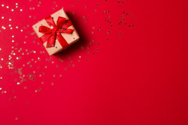 Weihnachtszusammensetzung grußkarte. geschenk aus kraftpapier auf einem roten mit einem goldenen stern konfetti