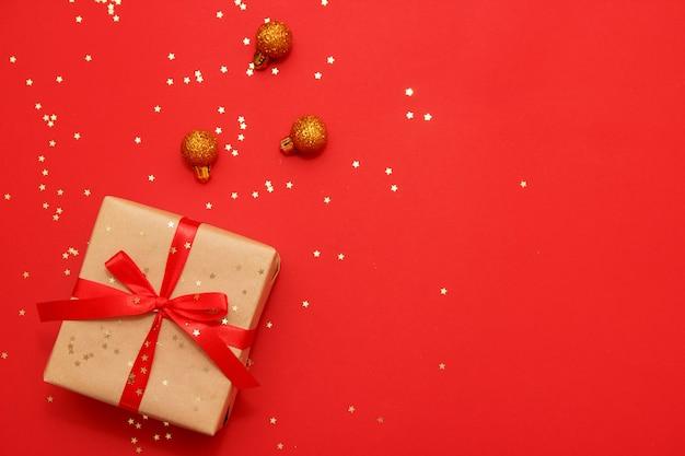 Weihnachtszusammensetzung grußkarte. geschenk vom kraftpapier mit goldenen bällen auf einem roten hintergrund