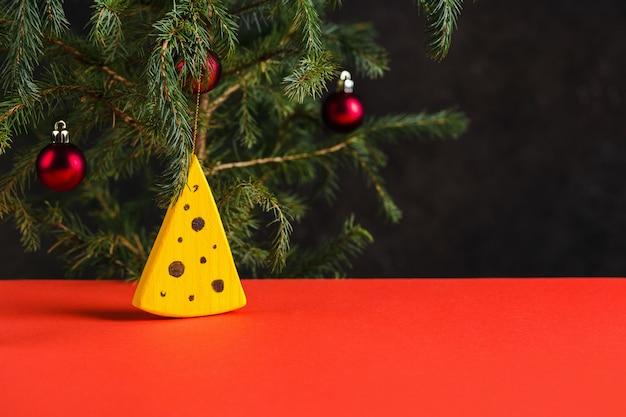 Weihnachtszusammensetzung. künstlicher käse und spielwaren auf dem weihnachtsbaum. roter hintergrund