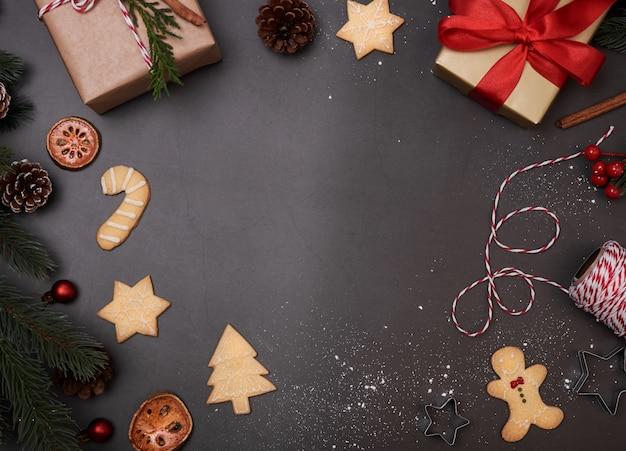 Weihnachtszusammensetzung mit dekorationen und geschenkbox mit weihnachtsplätzchen auf schwarzem hintergrund.