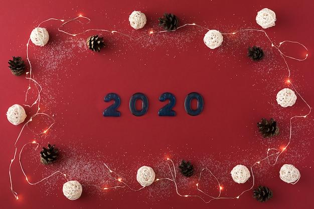 Weihnachtszusammensetzung mit girlande, tannenzapfen, 2020 und weißen bällen auf rot