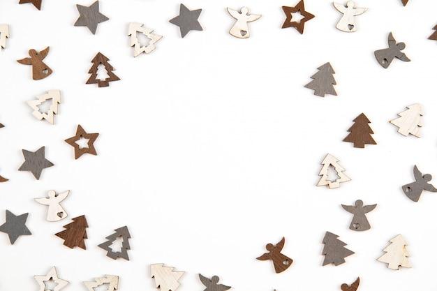 Weihnachtszusammensetzung mit hölzernen dekorationen über dem weißen hintergrund. saisonale feiertage, grußkarte, einladung für weihnachtsfeier