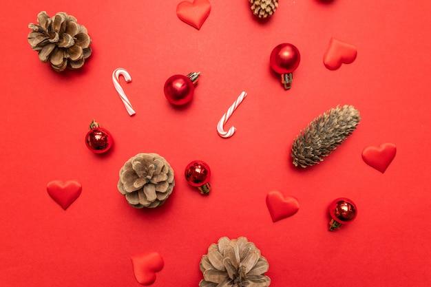 Weihnachtszusammensetzung mit kiefernkegeln, silberne sterne der weihnachtsdekoration, zuckerstangen auf rot