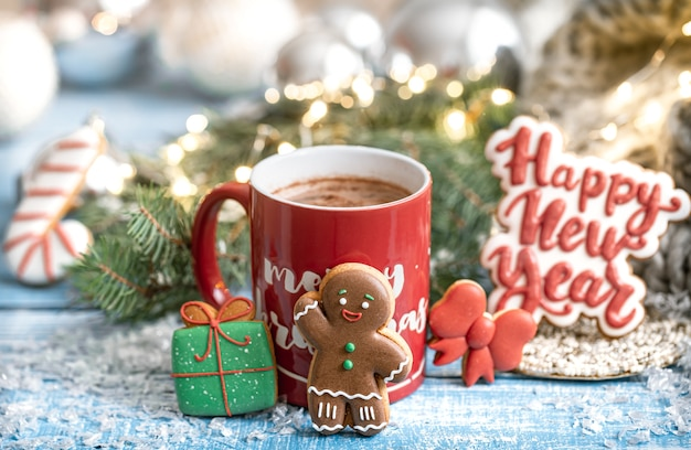 Weihnachtszusammensetzung mit lebkuchenplätzchen und roter tasse heißes getränk auf unscharfem hintergrund.