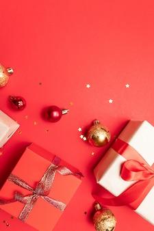 Weihnachtszusammensetzung mit rotem präsentkarton, bändern, rotem goldgroßen und bällchen, feiertagsdekorationen auf rot. flache lage, draufsicht, copyspace