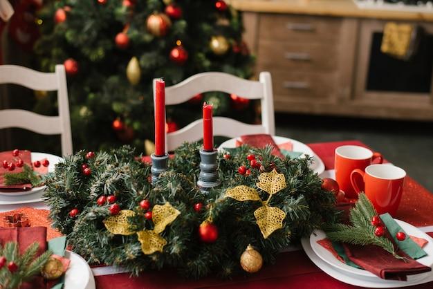 Weihnachtszusammensetzung mit roten kerzen auf einer festlichen tabelle mit einer roten tischdecke
