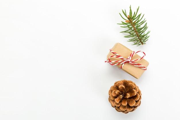 Weihnachtszusammensetzung mit tannenzapfentannenzweigen und weihnachtsgeschenkbox. draufsicht, flach lag auf weiß
