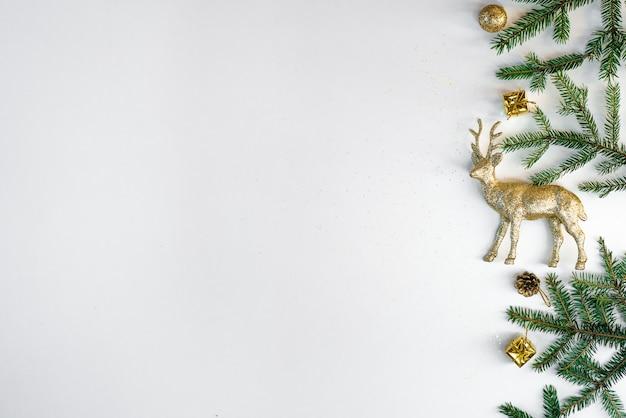 Weihnachtszusammensetzung mit tannenzweigen, goldenen rotwild und weihnachtsdekoration
