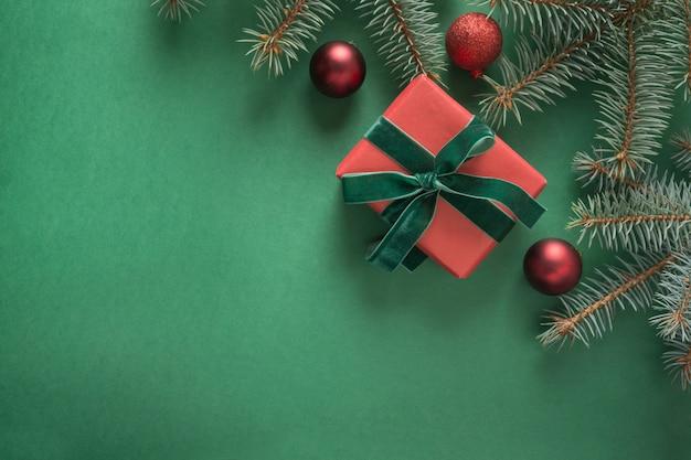 Weihnachtszusammensetzung mit weihnachtsbaum und rotem geschenk auf grün. grußkarte. . . copyspace