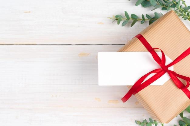 Weihnachtszusammensetzung mit weihnachtsgeschenk auf hölzernem hintergrund