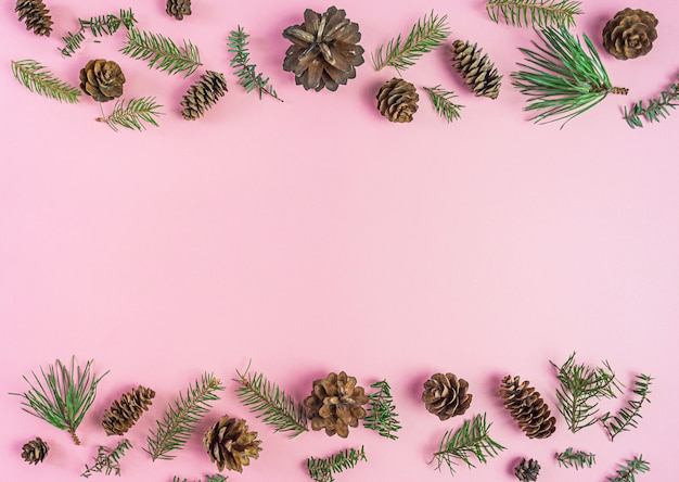 Weihnachtszusammensetzung. nadelbaumaste und feuerkegel auf rosa. weihnachten, winter. flachgelegt, draufsicht
