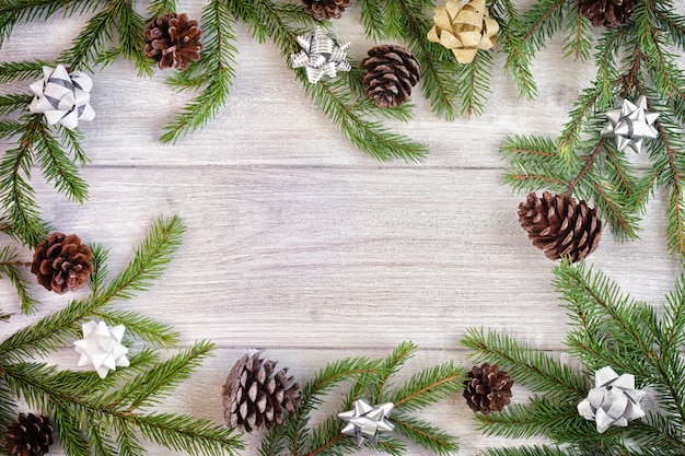 Weihnachtszusammensetzung, rahmen. fichtenzweige mit goldenen und silbernen schleifen und zapfen, kreisförmig angeordnet. in der mitte des copy space.