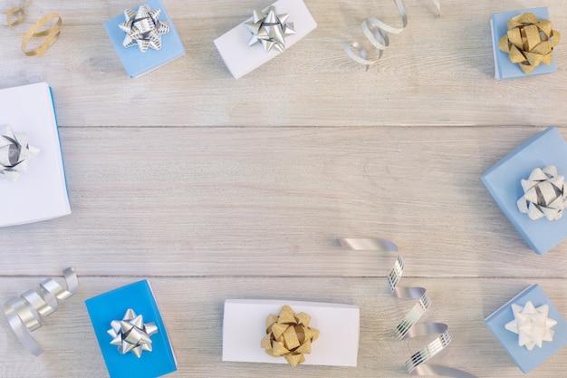 Weihnachtszusammensetzung, rahmen. kleine weiße und blaue geschenkboxen, bänder und schleifen.