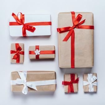 Weihnachtszusammensetzung verschiedener geschenkboxen, eingewickelt in handwerk und weißes papier und verziert mit satinroten bändern