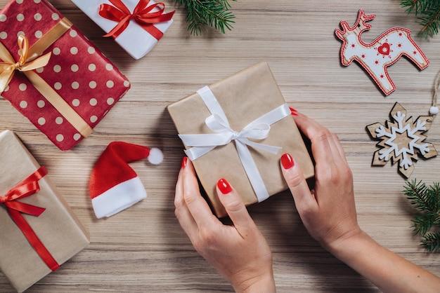 Weihnachtszusammensetzung von geschenkboxen, kiefernzweigen und geschenkboxen auf holztisch