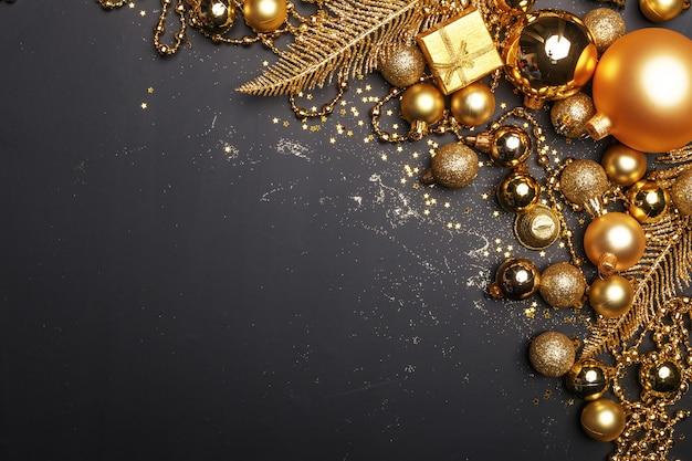 Weihnachtszusammensetzung von goldenen weihnachtsspielwaren und von dekorationselementen auf einem schwarzen hintergrund.