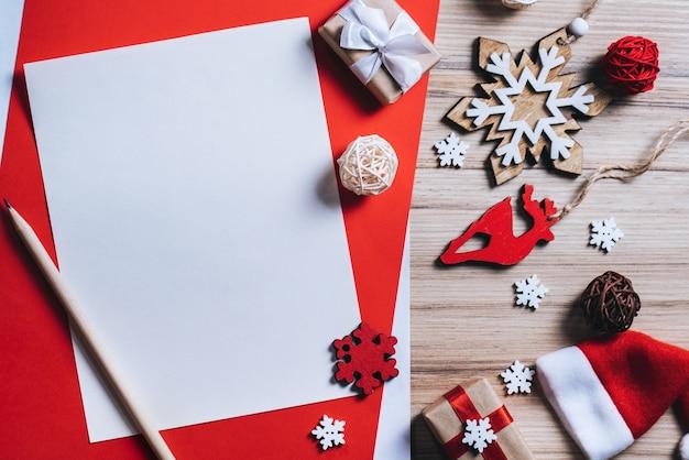 Weihnachtszusammensetzung von kieferndekorationen und geschenkboxen mit leerem stück papier
