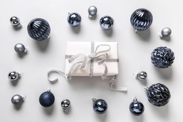 Weihnachtszusammensetzung von klassischen blauen bällen und von giftbox auf grau. ansicht von oben. weihnachten. feiertagsgrußkarte