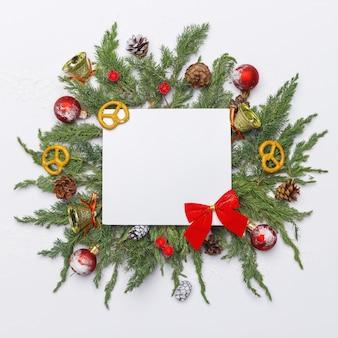 Weihnachtszusammensetzung von nadelbäumen, von dekorationen und von bonbons auf hellem hintergrund. flach liegen. draufsicht natur-neujahrskonzept. kopieren sie platz.