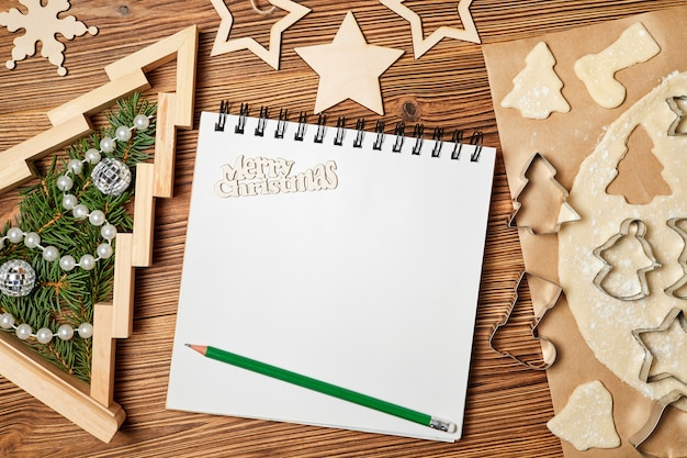 Weihnachtszusammensetzung von offenem leerem notizblock rohem lebkuchen weihnachtsplätzchen und neujahrsbaum