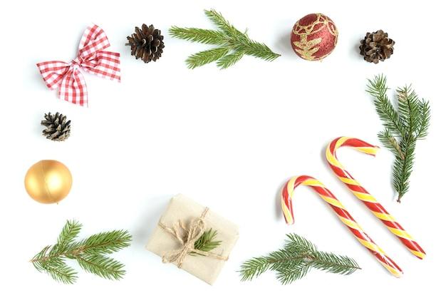Weihnachtszusammensetzung von tannenzapfen, tannenzweigen, weihnachtsstöcken, geschenkbox. draufsicht, flach liegen