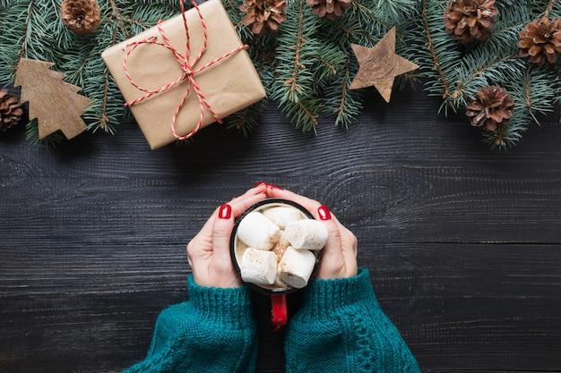 Weihnachtszusammensetzung von tannenzweigen, von hölzernen spielwaren und von gemütlichem getränkekaffee mit eibischen auf hölzernem brett