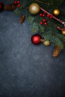 Weihnachtszusammensetzung von tannenzweigen, von weihnachtsbällen des rotes und des goldes und von süßigkeit, kiefernkegel.