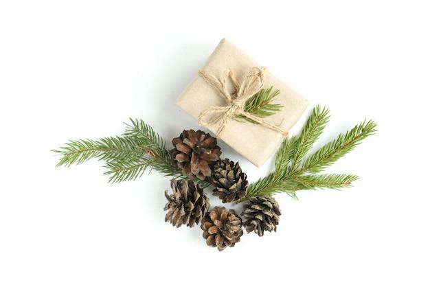 Weihnachtszusammensetzung von weihnachtskugeln, geschenkbox, zapfen und tannenzweigen lokalisiert auf weißer oberfläche. flache lage, draufsicht, kopierraum