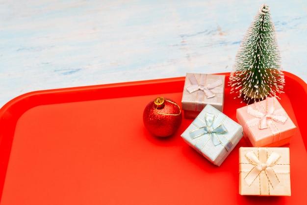 Weihnachtszusammensetzung. weihnachtsgeschenk-boxen. rotes plastikessentablett auf dem tisch.